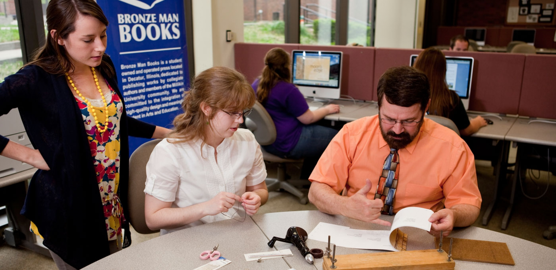 This photo shows faculty member Dr. Brooks flipping through a book with two students at a Bronze Man Books event.