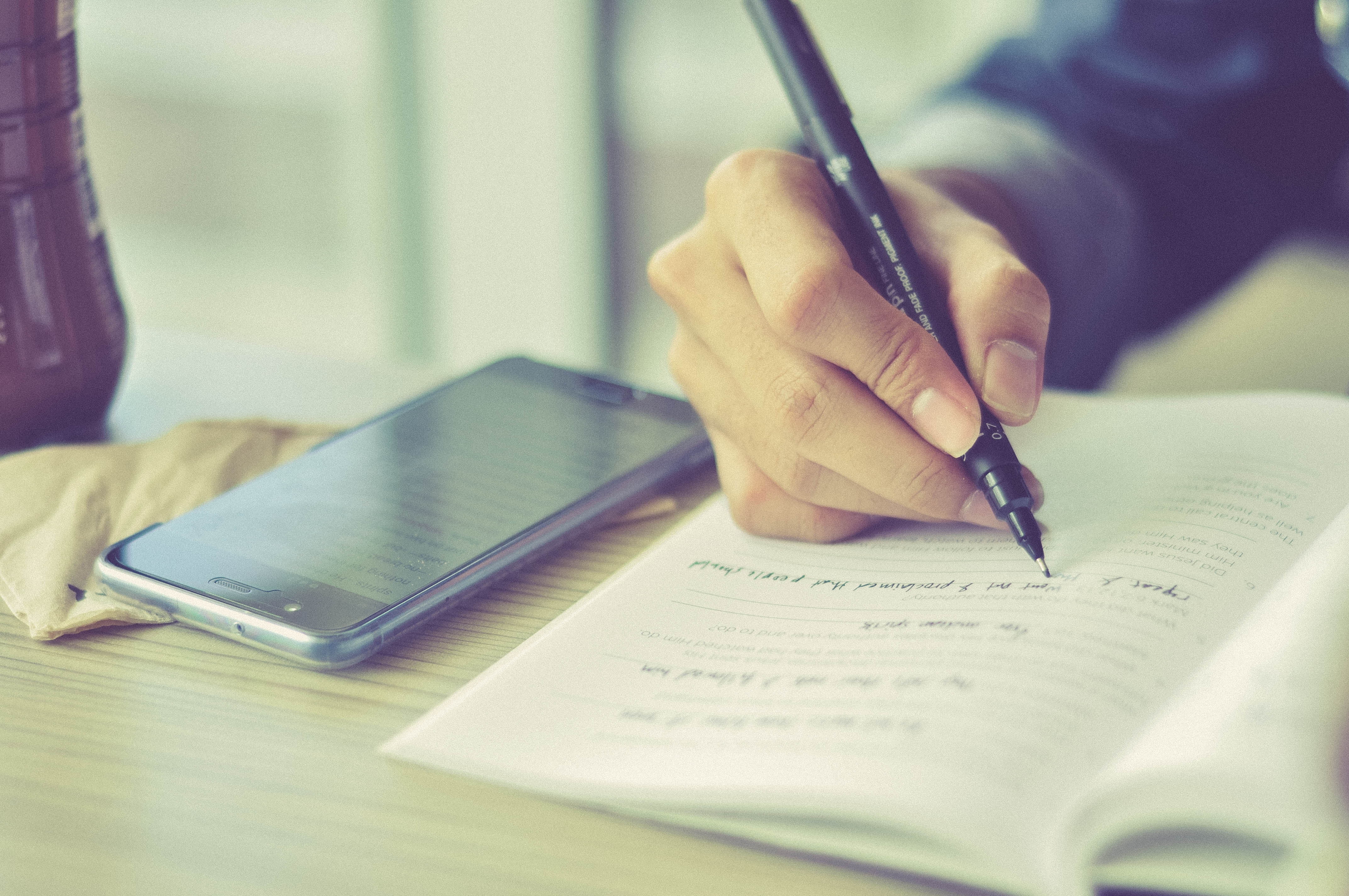 A close-up image of a person writing in a notebook, with a phone laying next to the notebook.