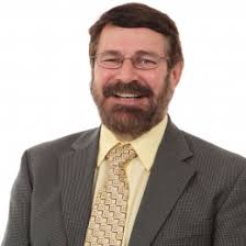 Dr. Randy Brooks, who has short brown hair and wire glasses. He is wearing a grey suit with a yellow shirt and yellow, printed tie.